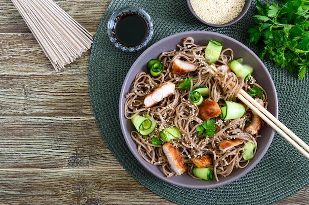 Zimna soba z kurczakiem, świeżymi ogórkami, sosem i sezamem. klasyczna zimna sałatka z makaronem gryczanym. japońskie jedzenie. tradycyjna kuchnia azjatycka. widok z góry, leżał płasko.