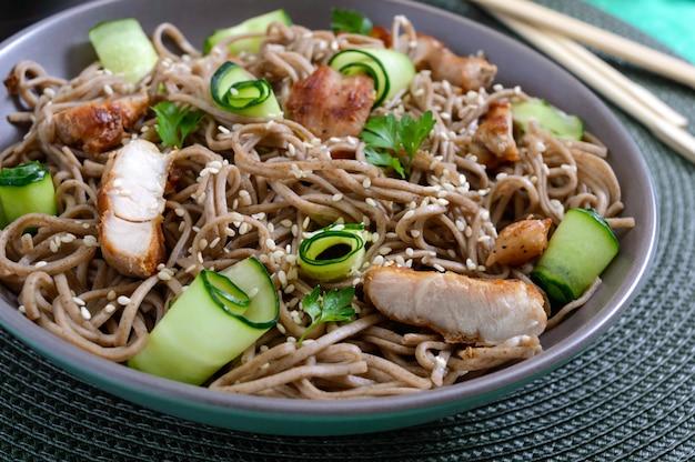 Zimna soba z kurczakiem, świeżymi ogórkami, sosem i sezamem. klasyczna zimna sałatka z makaronem gryczanym. japońskie jedzenie. tradycyjna kuchnia azjatycka