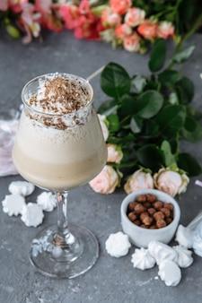 Zimna świeża kawa mrożona z czekoladą, przyozdobiona ciastkami i słodyczami.