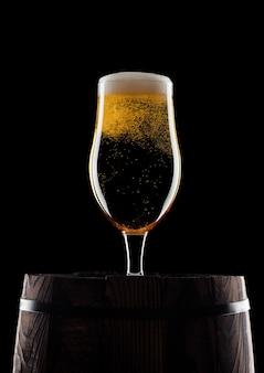Zimna szklanka piwa rzemieślniczego na starej drewnianej beczce na czarnym tle z rosą i bąbelkami