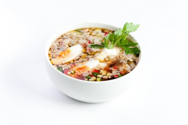 Zimna zupa jarzynowa z kwasem, jajkami i pietruszką, na białym tle