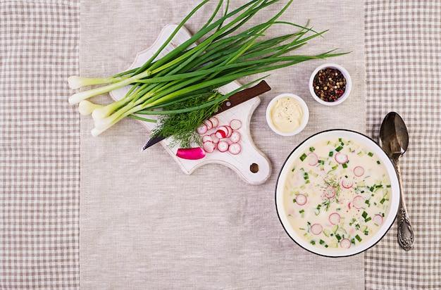 Zimna zupa ze świeżymi ogórkami, rzodkiewkami, ziemniakami i kiełbasą z jogurtem w misce. tradycyjne rosyjskie jedzenie - okroshka. letnia zupa na zimno. widok z góry. leżał płasko