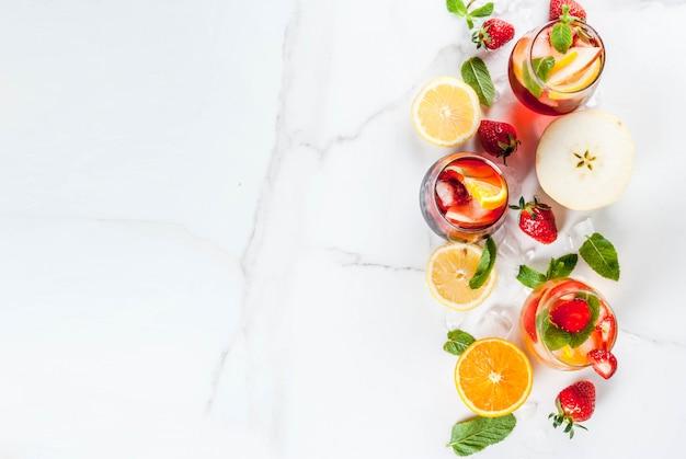 Zimne białe różowe i czerwone koktajle sangria z jagodami świeżych owoców i miętą.