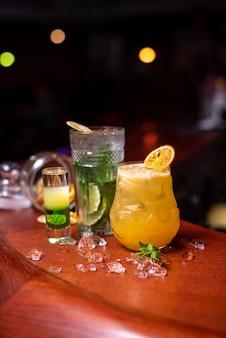 Zimne letnie pyszne koktajle z limonką, miętą i lodem w szklance z kroplami. wielobarwny napój koktajlowy alkohol w barze.