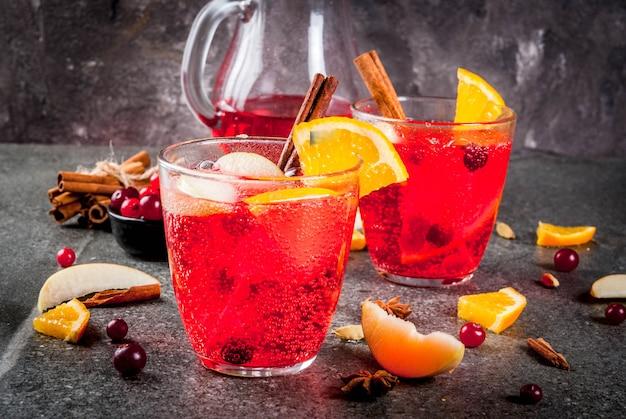 Zimne napoje na jesień i zimę, żurawinowy i pomarańczowy świąteczny poncz z cynamonem, gwiazdkami anyżu, na czarnym copyspace