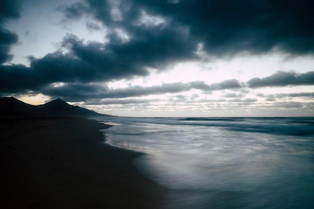 Zimne odcienie morza i brzegu po zachodzie słońca podczas wieczornego świtu przed nocą - nikt tam nie ma ludzi i długa ekspozycja - niebieskie kolory dla malowniczego krajobrazu wybrzeża