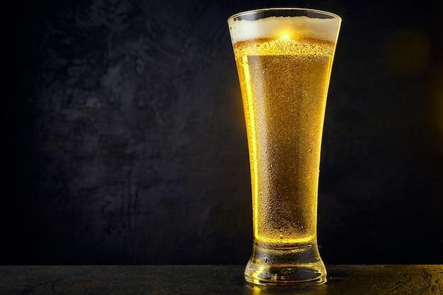 Zimne piwo jasne piwo w szklance z kroplami na ciemnym stole. kufel piwa na czarnym tle.