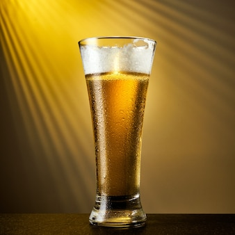 Zimne piwo jasne piwo w szklance z kroplami na ciemnym stole. kufel piwa na żółtym tle.