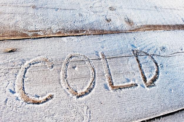 Zimno napisane na drewnianym florze z mrozem