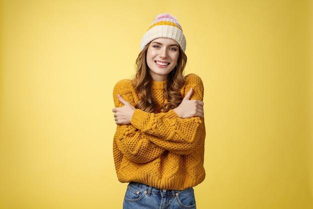 Zimno przynieś kurtkę. portret urocza delikatna kobieca ładna dziewczyna obejmując się przytulając uśmiechając się ciepłe spojrzenie zamrażanie na zewnątrz stojący dzianinowy sweter kapelusz, żółte tło