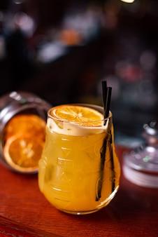 Zimny alkoholowy koktajl cytrusowy z sokiem pomarańczowym i limonkową miętą i lodem w szklance przy barze