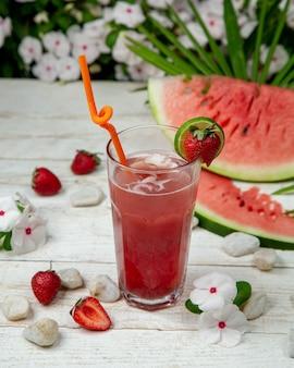 Zimny arbuz truskawkowy kuice z kostkami lodu i owocami dookoła.