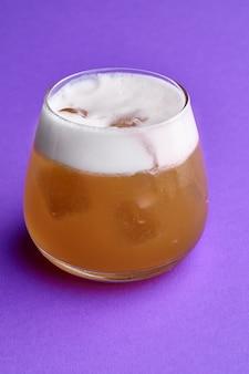 Zimny koktajl green fizz - gin, likier melonowy na fioletowym tle.