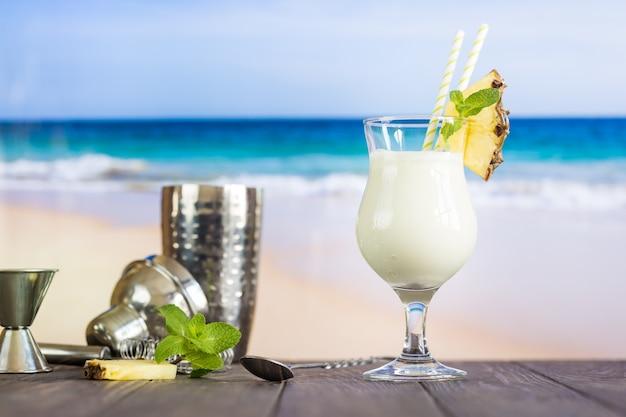 Zimny koktajl pina colada w szklance na plaży z powierzchnią seascape