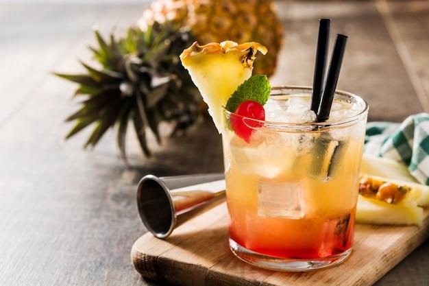 Zimny koktajl z ananasem i wiśnią na drewnianym stole