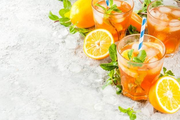 Zimny letni napój. mrożona herbata z cytryną i miętą na szarym tle kamienia.