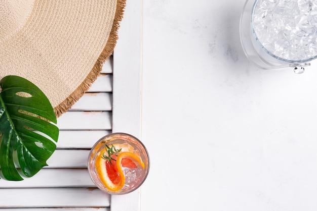 Zimny letni napój w szklance z plasterkiem grejpfruta i kostkami lodu oraz kapeluszem z szerokim rondem i zielonym liściem rośliny tropikalnej