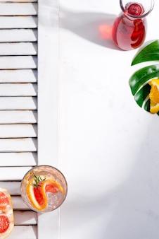Zimny letni napój w szklance z plasterkiem grejpfruta i kostkami lodu