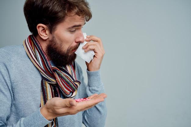 Zimny mężczyzna z szalikiem na szyi grypa problemy zdrowotne jasne tło
