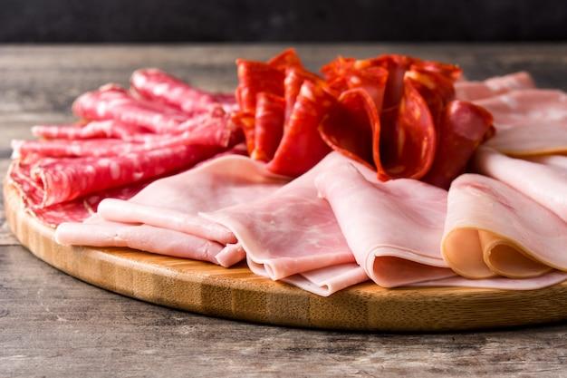 Zimny mięso na tnącej desce na drewnianym stole. szynka, salami, mortadela kiełbasiana i indyk z bliska