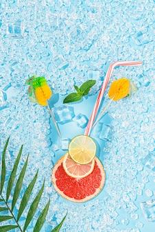 Zimny napój. lód na jasnoniebieskim tle ułożonym w formie kieliszka z rurką na koktajl i plasterek grejpfruta