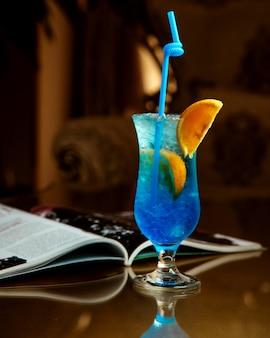 Zimny napój w kolorze niebieskim z plasterkiem pomarańczy