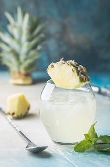 Zimny orzeźwiający napój ananasowy z lodem na gorący letni dzień, na niebieskim tle