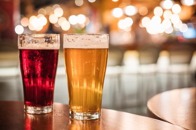 Zimny piwny szkło na prętowym lub karczemnym biurku z bokeh ludźmi biznesu
