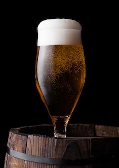 Zimny szkło rzemieślniczy piwo na starej drewnianej baryłce na czarnym tle