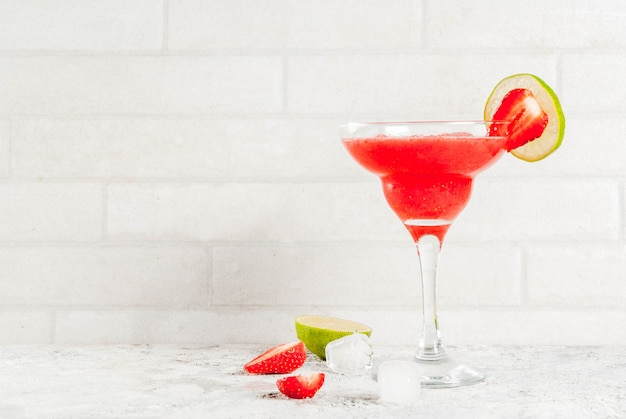 Zimny truskawkowy koktajl margarita z lodem, limonką i świeżymi jagodami w szklance margarita