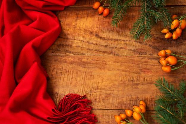 Zimowa, ciepła atmosfera. rama z czerwonym szalikiem, różane jagody i świerk na drewniane tła. zimowy wieczór. układ płaski, układ, miejsce na tekst, kartka pocztowa, wysoka rozdzielczość