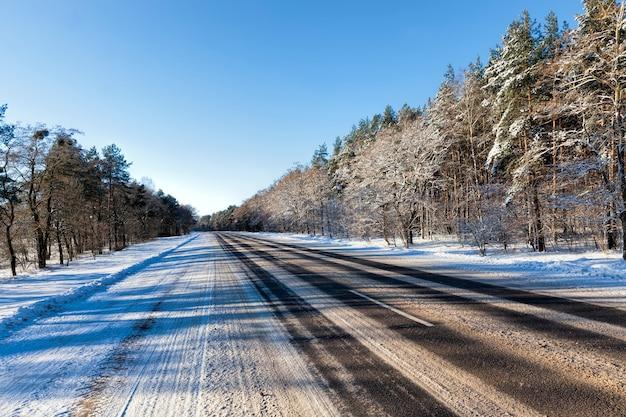 Zimowa droga do kierowania samochodami w sezonie zimowym, pokryta śniegiem po opadach śniegu