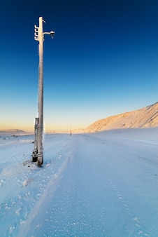 Zimowa droga w górach. nieaktywna kolumna oświetleniowa.