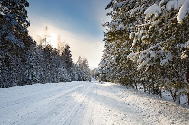 Zimowa droga z chłodnym zachodem słońca i śniegiem