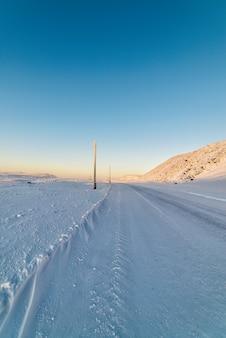 Zimowa droga, zaśnieżone stoki. starsze nieaktywne słupy oświetleniowe.