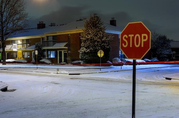 Zimowa dzielnica mieszkaniowa na ulicy w nocy z zaparkowanymi samochodami pokrytymi śniegiem