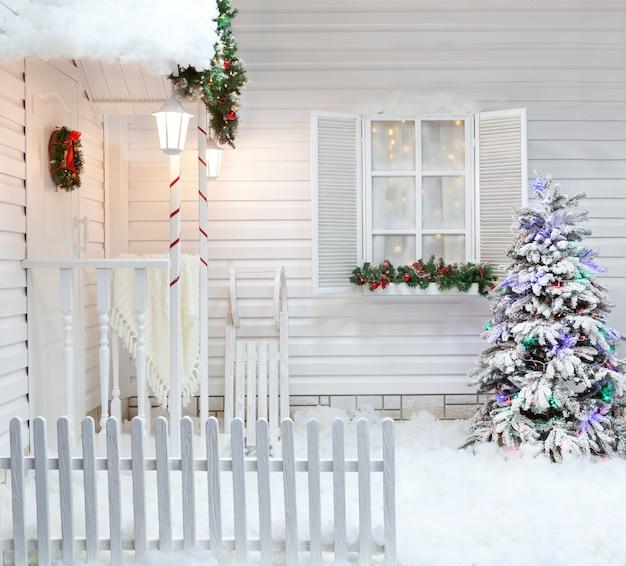 Zimowa fasada wiejskiego domu z dekoracjami świątecznymi w amerykańskim stylu.