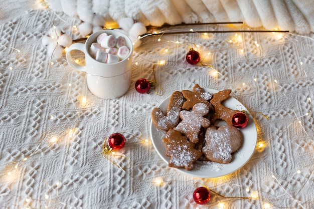 Zimowa gorąca czekolada z piankami i ciasteczkami imbirowymi, świąteczna lekka girlanda i czerwone zabawki choinkowe na białym łóżku