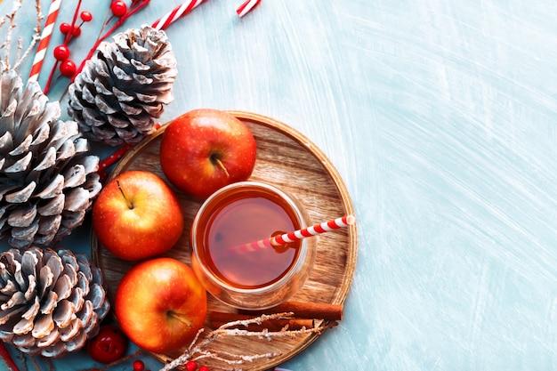 Zimowa gorąca herbata w szkle z jabłkami i przyprawami na drewnie