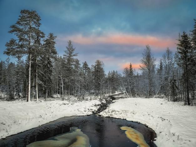 Zimowa górska rzeka w karelii przepływa przez las
