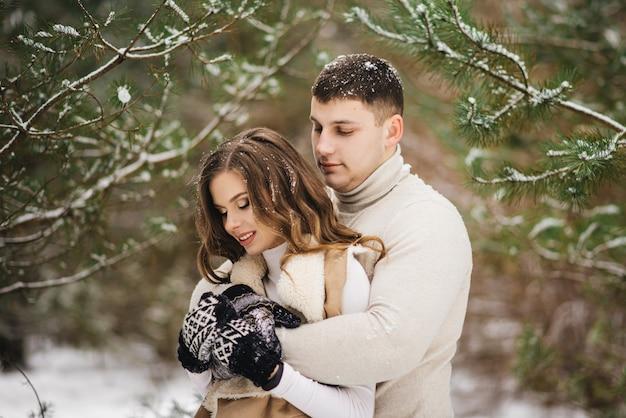 Zimowa historia miłosna na lodzie. stylowi kochankowie chłopiec i dziewczynka na śniegu. romans
