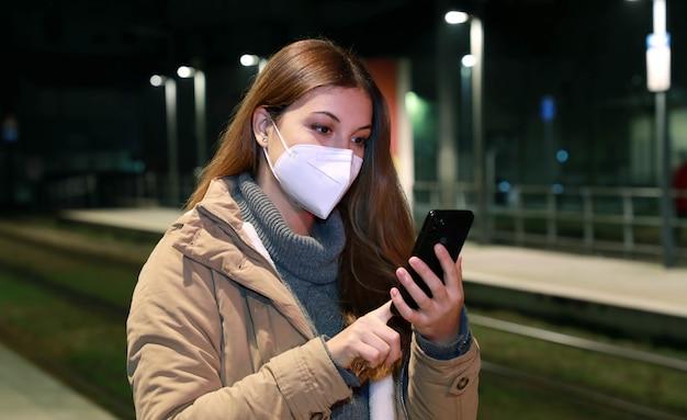 Zimowa kobieta w masce ochronnej kn95 ffp2 za pomocą smartfona czeka w nocy na pociąg na pustej stacji