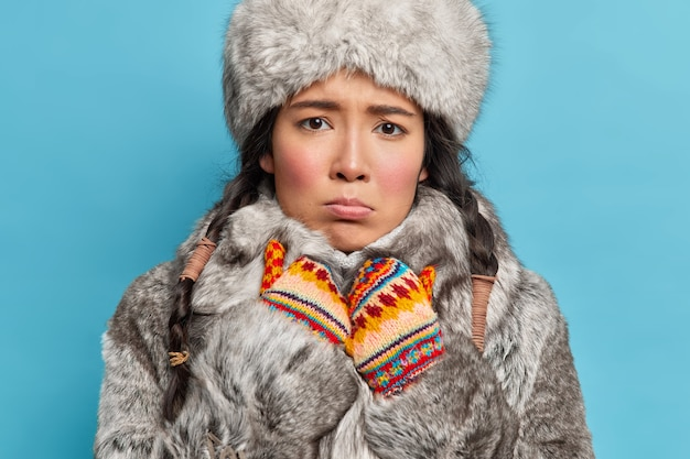 Zimowa kobieta wygląda smutno z przodu, czuje zimno ubrana w szarą futrzaną czapkę i płaszcz ciepłe dzianinowe rękawiczki ubrane na zimową pogodę odizolowane na niebieskiej ścianie