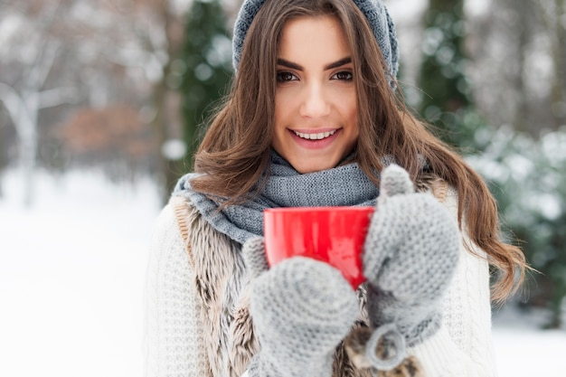 Zimowa kobieta z filiżanką gorącej herbaty