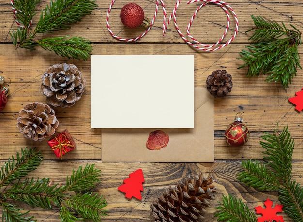 Zimowa kompozycja bożonarodzeniowa z pustą kartką i kopertą nad drewnianym stołem