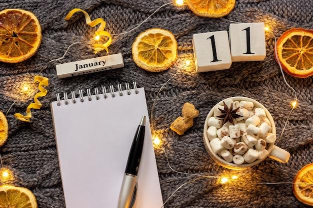 Zimowa kompozycja. drewniany kalendarz 11 stycznia kubek kakao z pianką, pusty otwarty notatnik