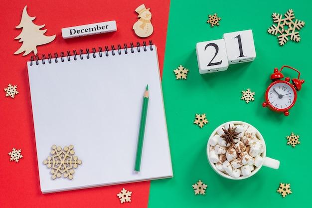 Zimowa kompozycja. drewniany kalendarz 21 grudnia kubek kakao z pianką, pusty otwarty notatnik z ołówkiem,