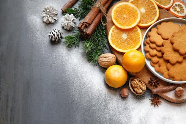 Zimowa kompozycja. płaskie ułożenie piernika, laski cynamonu, szyszki, gałązki świerku, plasterki pomarańczy, mandarynka, orzechy, cukier puder na czarnym tle.