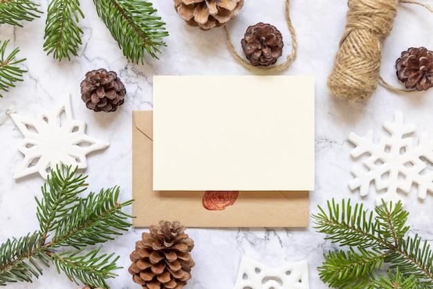 Zimowa kompozycja świąteczna z kartą na zaklejonej kopercie flat lay