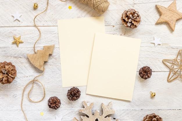 Zimowa kompozycja świąteczna z kartami płasko leżał. boże narodzenie i nowy rok szablon karty z pozdrowieniami z szyszek, drewniane dekoracje i liny na marmurowym tle widok z góry. makieta wakacje.